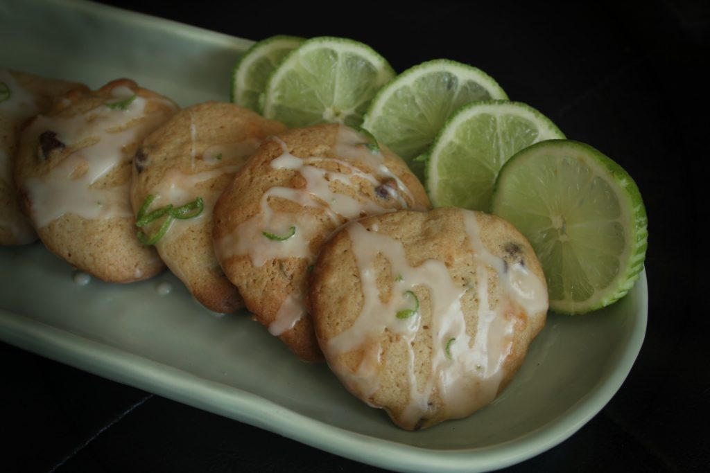 key lime chocolate chip cookies with icing on a green oblong plate with limes