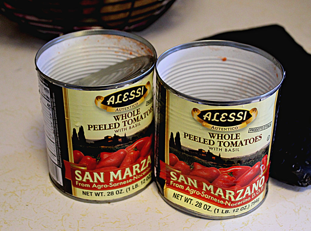 two cans of San Marzano tomatoes opened on the counter getting ready to make into he bacon tomato soup