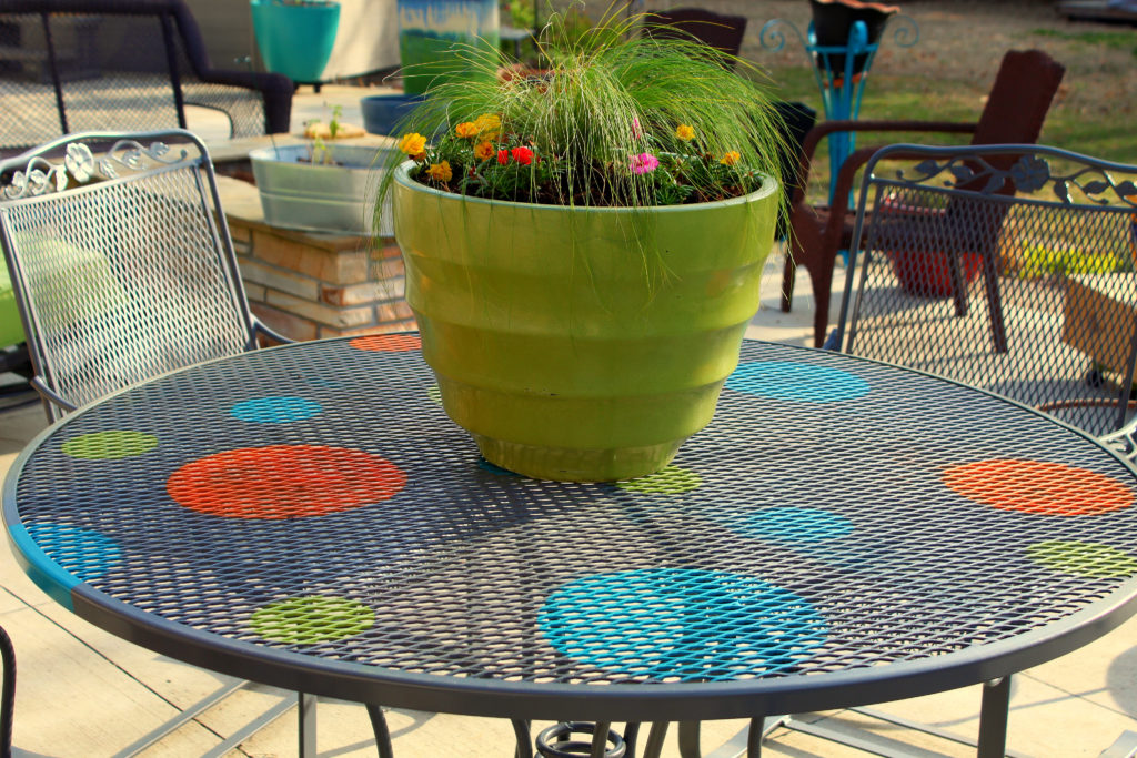 Finished wrought iron redo table on the back patio with a green planter and grass and flowers in it.