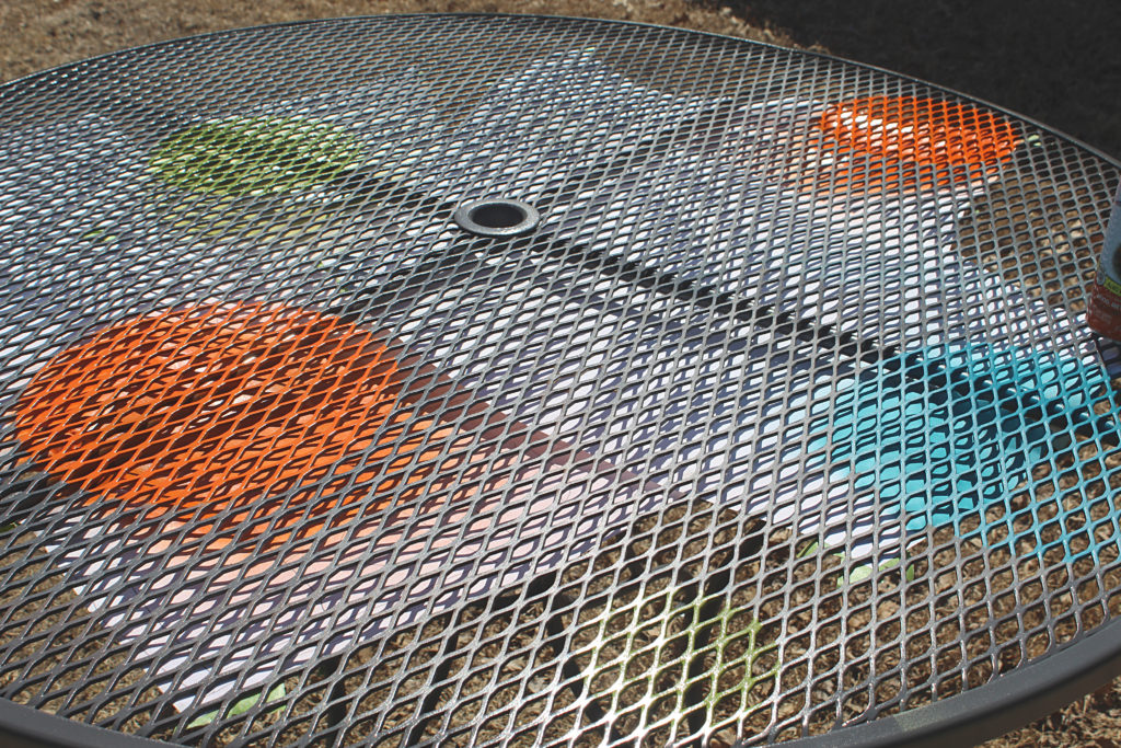 Beginning to spray stencils on table with orange blue and green paint on a grey table