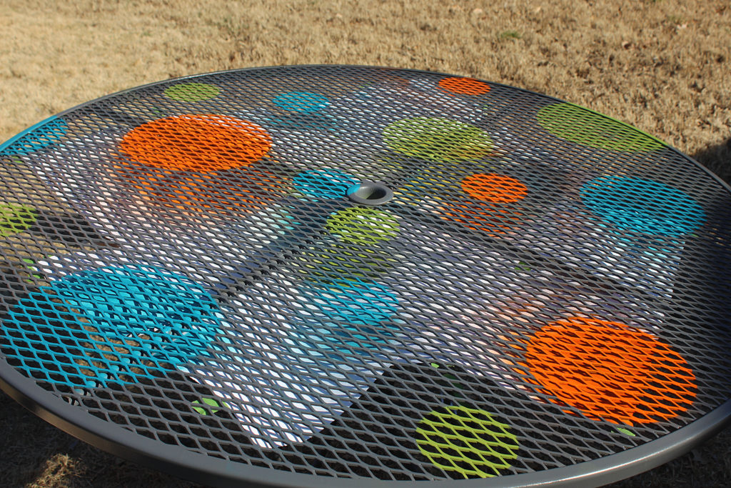 More sprayed dots all sizes on grey wrought iron patio table