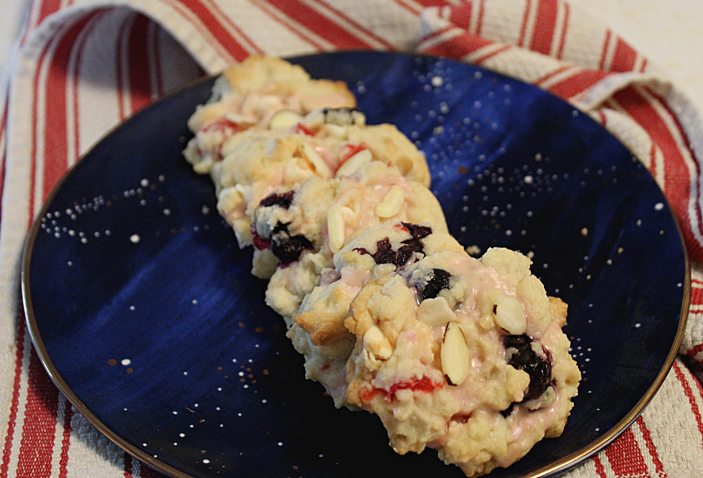 cherries and blueberries almond cookies on blue space plate
