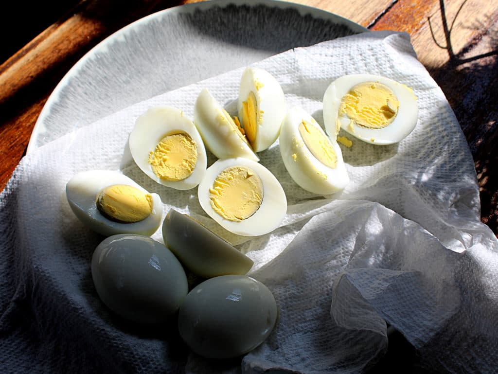 boiled egg halves on a paper towel on a gray plate