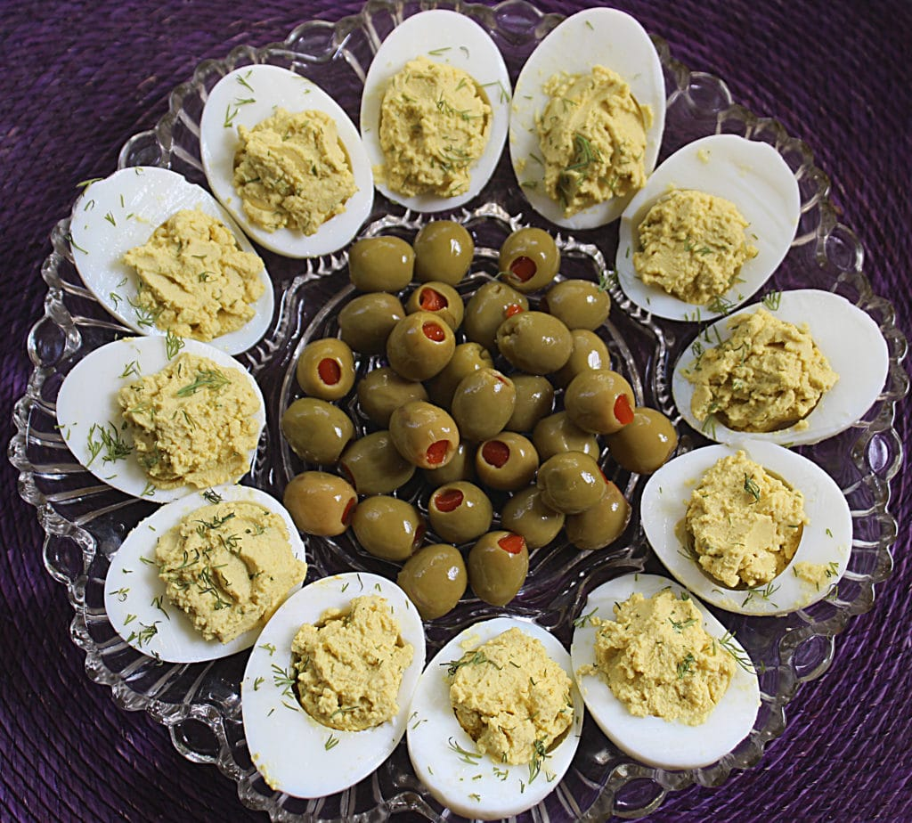 curry and fresh dill deviled eggs on a decorative plate with green olives in the center on a purple place mat