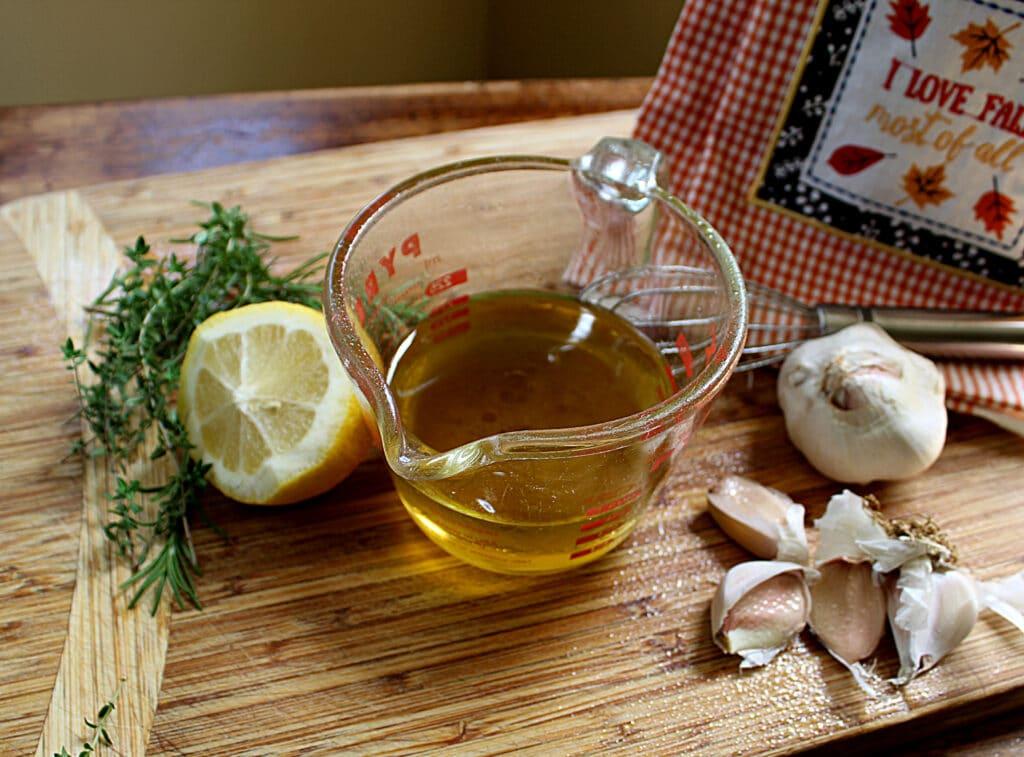 Olive oil, lemon, garlic, thyme, whisk on a cutting board