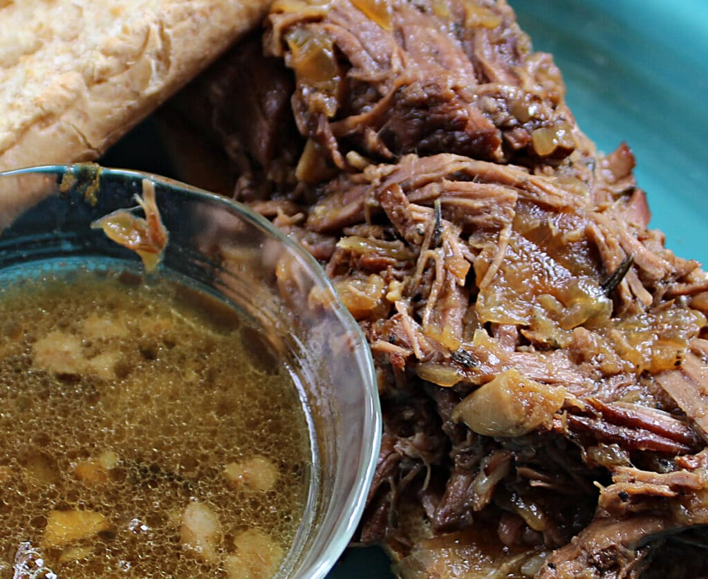 drip beef with cooked onions and garlic next to a bowl of au jus