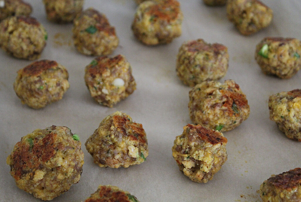 partially cooked sausage balls on a cookie tray with parchment paper