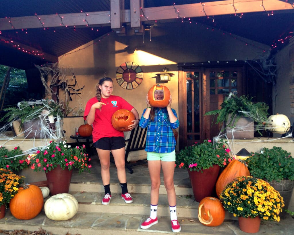 kids carving pumpkins on front decorated porch before halloween