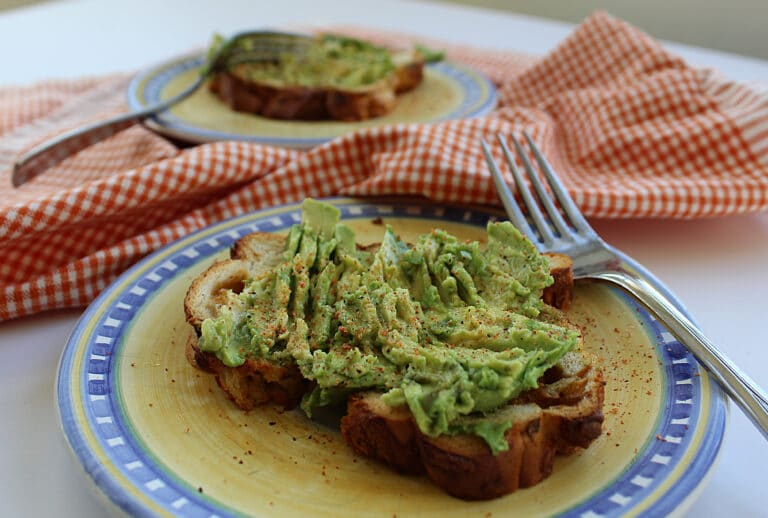 2 spicy avocado toasts on plates with forks