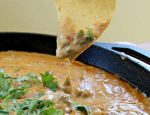 Spicy Rotel Sausage Cheese Dip with cilantro in a cast iron skillet on a tortilla chip close up