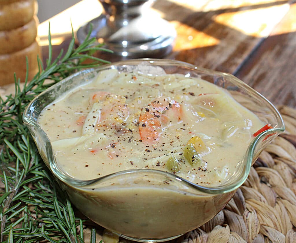 Seafood chowder in a glass bowl with rosemary leaves ready to serve.