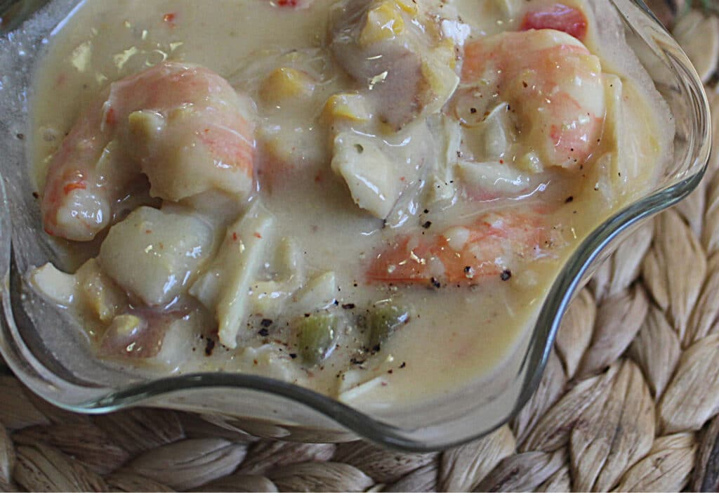 close up of seafood chowder in a glass bowl on a woven place mat