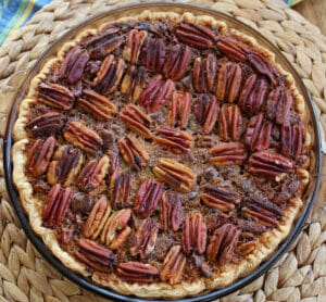 chocolate orange cointreau pecan pie baked in a glass pie plate on a woven place mat