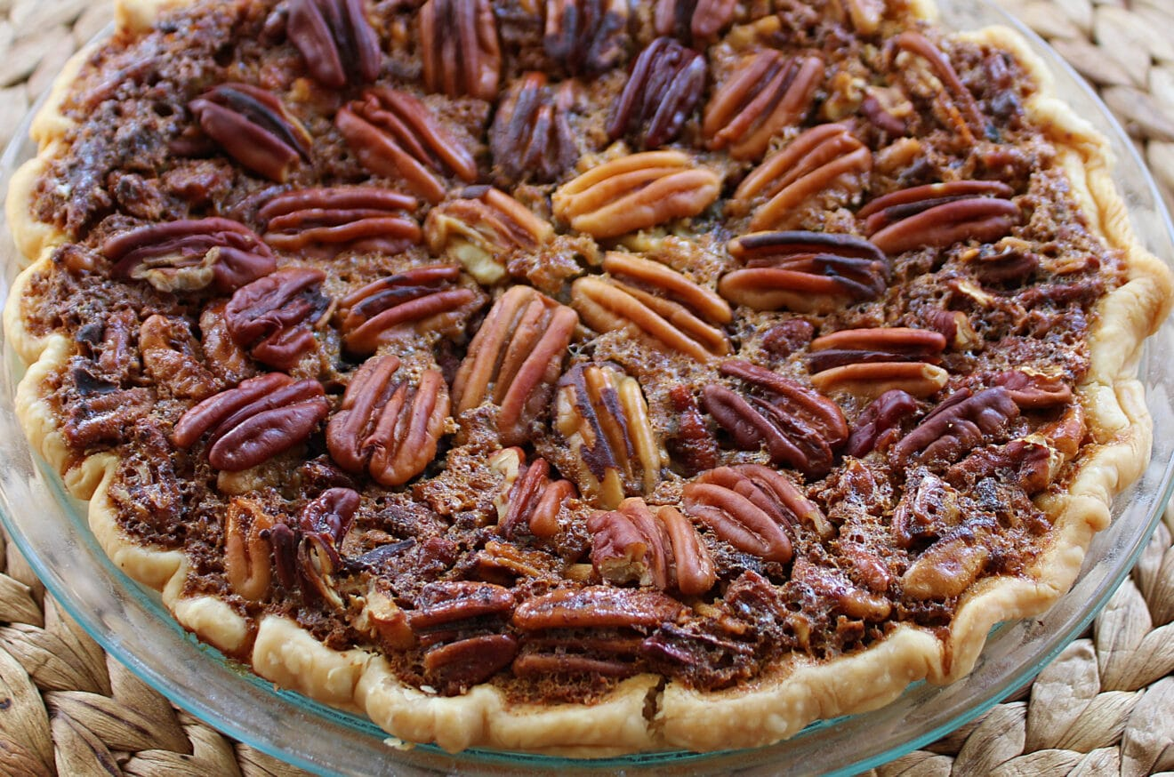 Baked pecan pie in a glass pie plate on a woven place mat