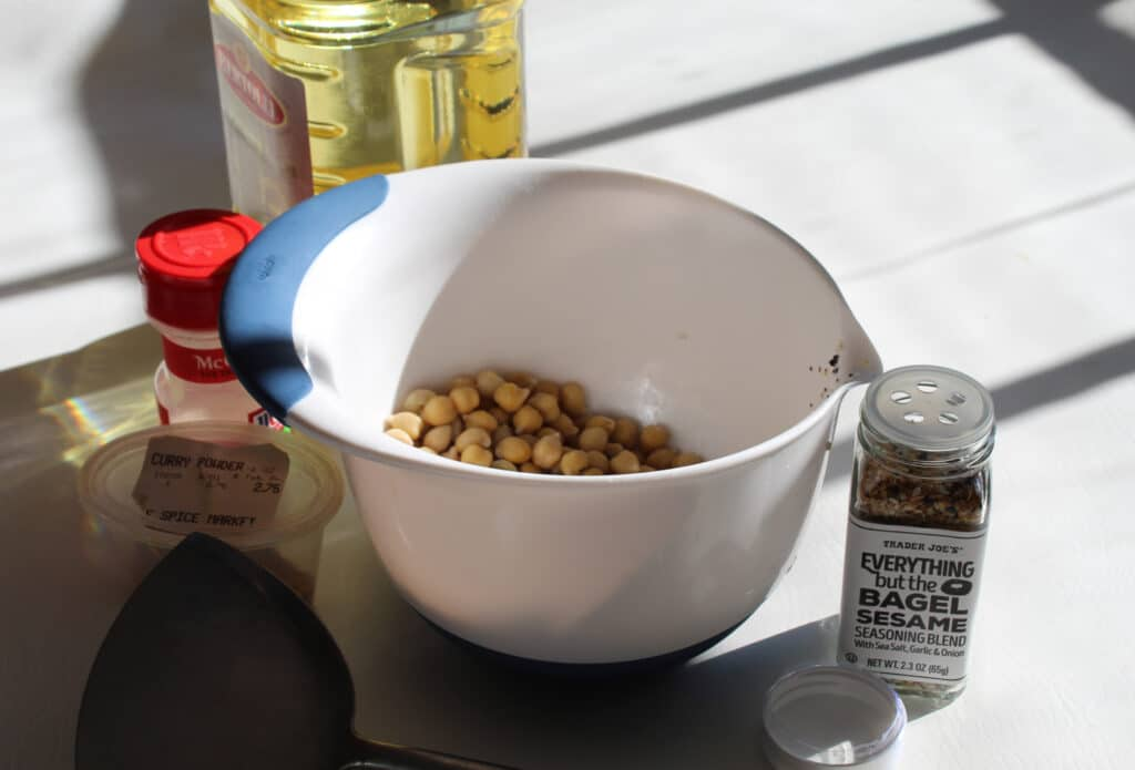 plain chickpeas in a white bowl with curry, garlic salt, everything seasoning, olive oil