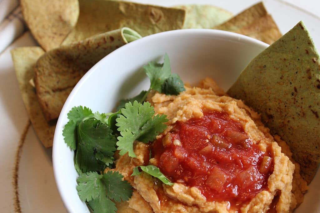 Homade hummus in a white bowl with cilantro and hot salsa on top. Served with homemade low carb spinach tortilla chips.