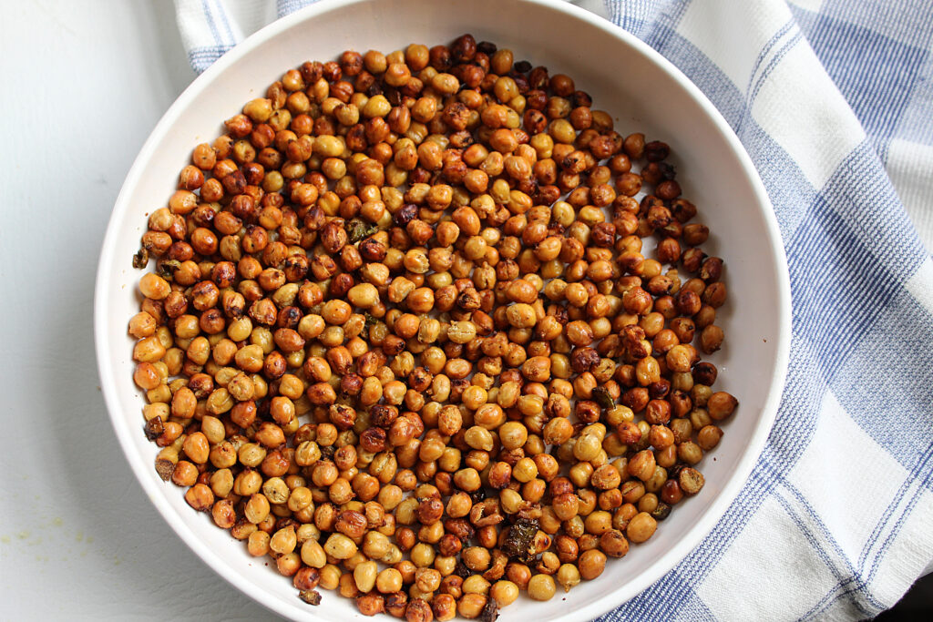 overhead shot of finished spicy roasted chickpeas with jalapenos in a white bowl with a blue and white towel.