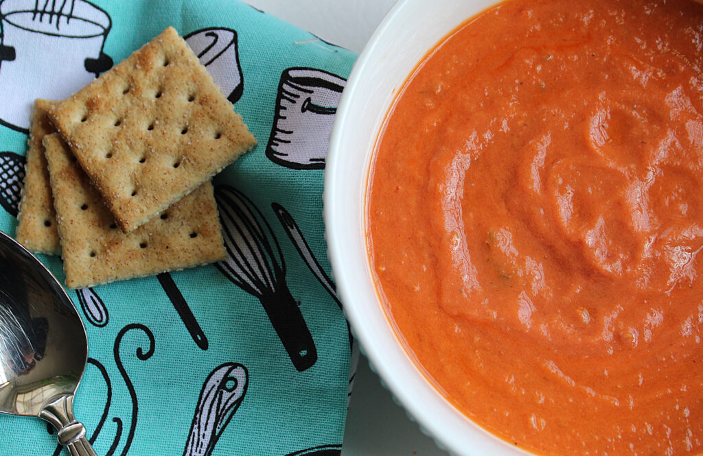 homemade bacon tomato soup in a white bowl with crackers on a blue towel