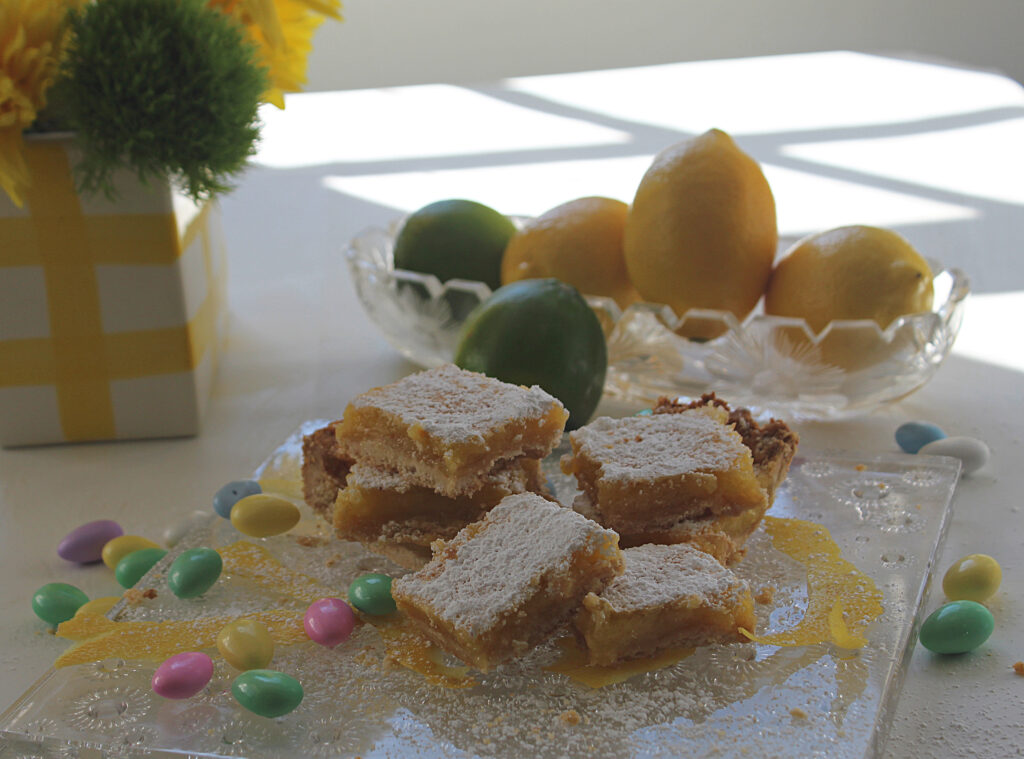 lemon bars on an Easter table with jordon almonds, flowers and fruit