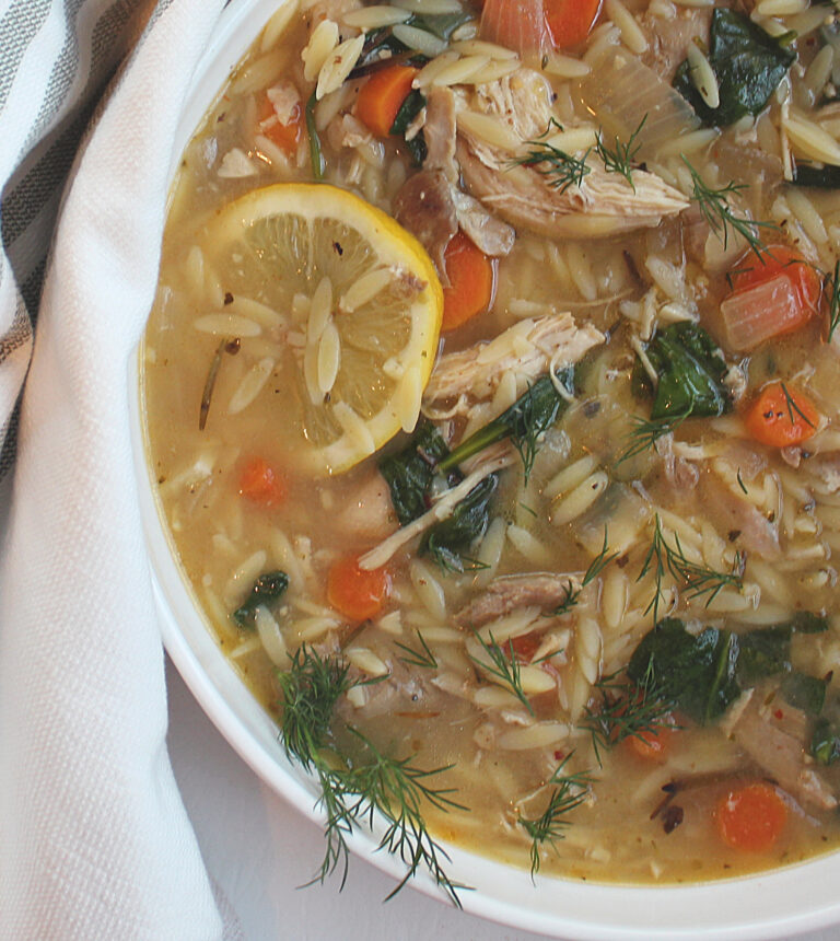 lemon chicken orzo soup in a white serving bowl