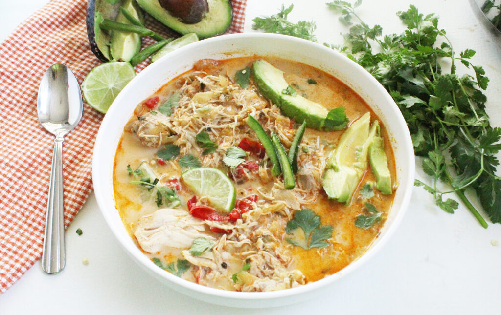 mexican chicken soup in a white bowl with avocado, cilantro and lime wedges