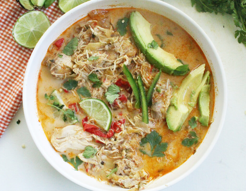 overhead photo of low carb mexican chicken soup in a white bowl with avocado and lime slimes