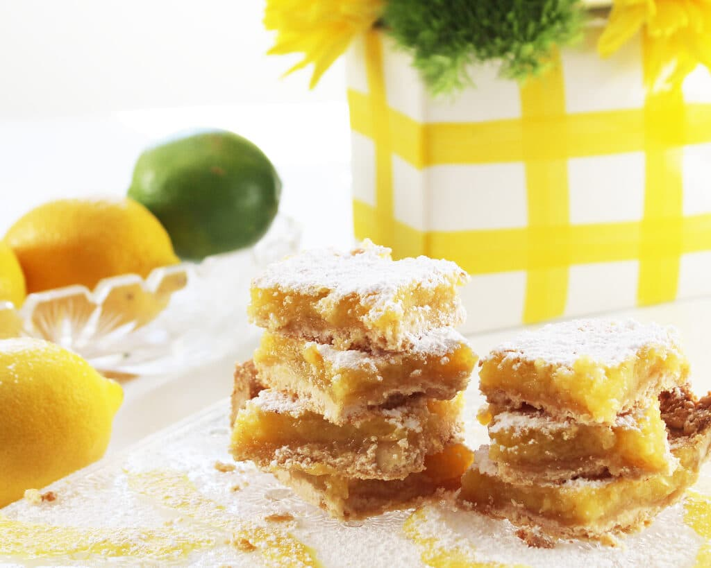 Stacked lemon bars on a crystal serving platter with lemons, limes and a flower vase