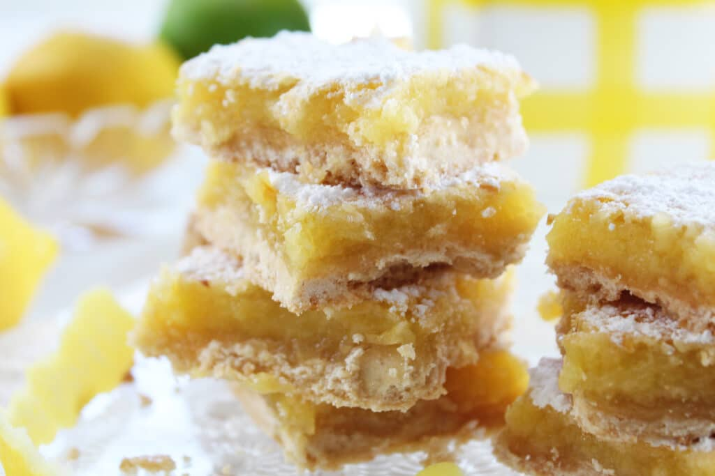 2 stacks or stacked lemon bars on a crystal plate