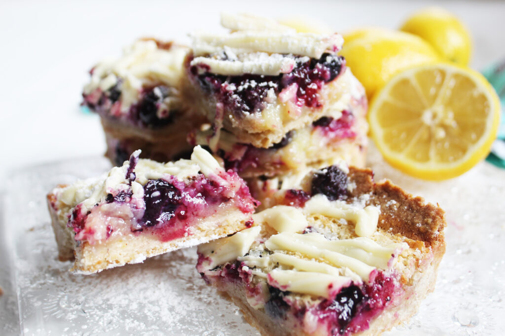 individual and stacks of white chocolate blueberry lemon bars on a crystal plate