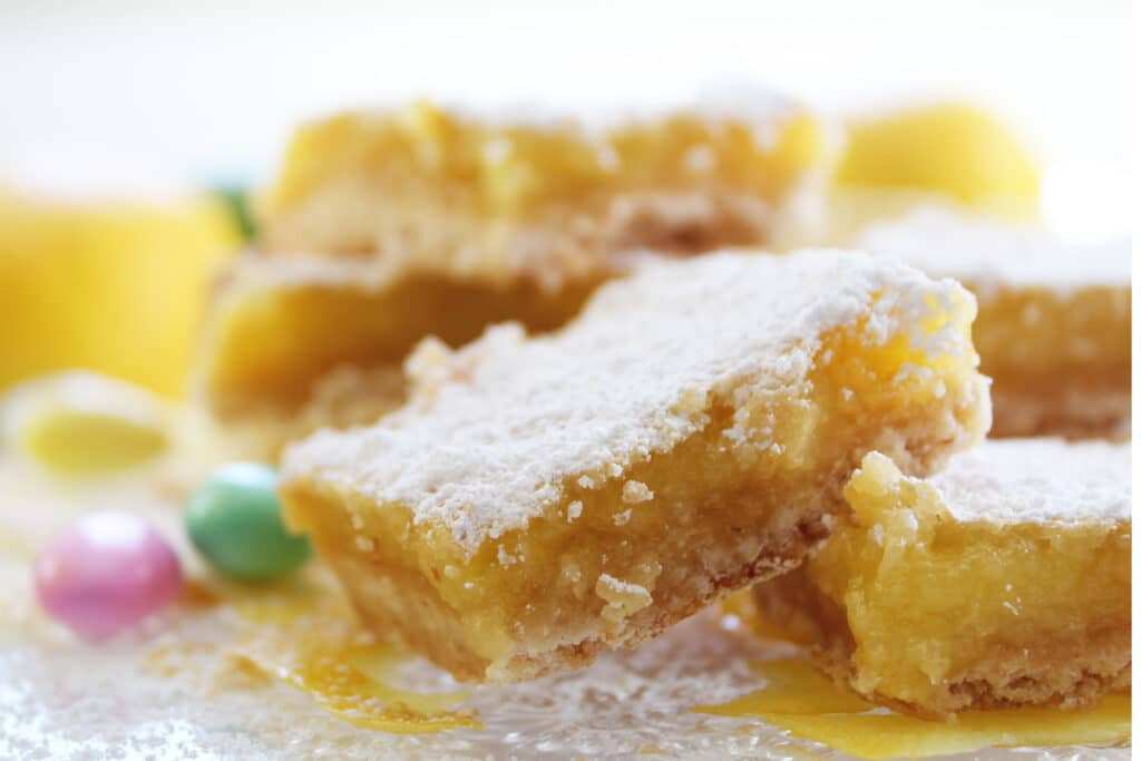 Close up of lemon bars with powdered sugar and jordan almonds on a crystal plate