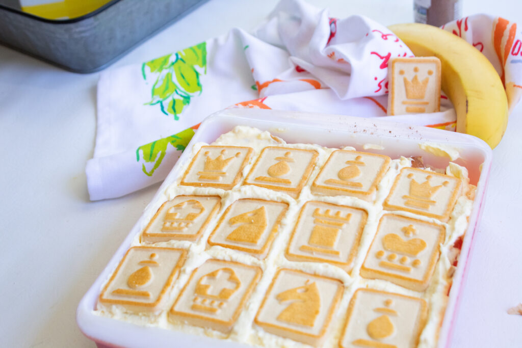 Small pan of banana pudding with chessman cookies on top and a banana and cookie on a towel in the background