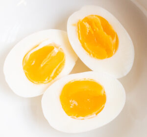 close up of 3 perfect soft boiled egg halves in a white bowl