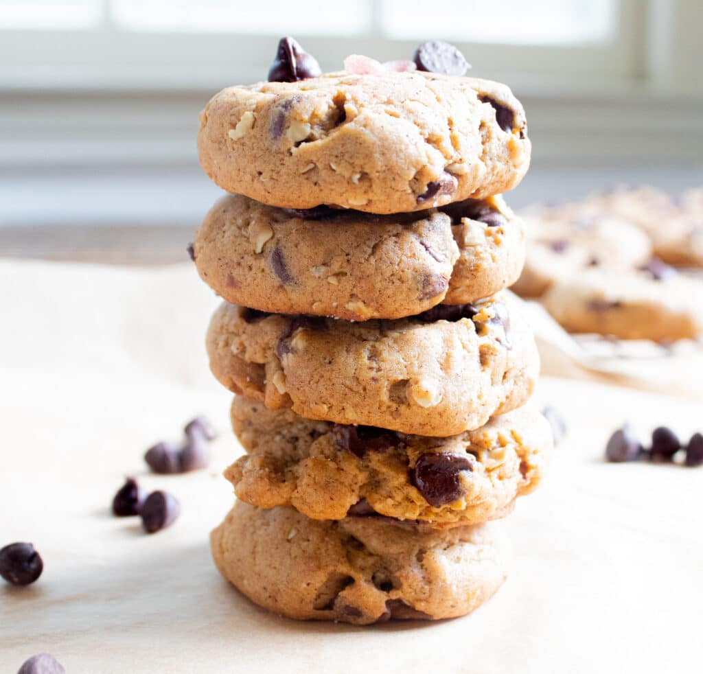 Stack of 5 easy pumpkin chocolate chip cookies with more cookies in the background and chocolate chips