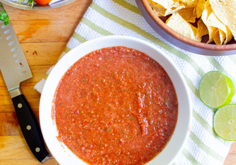 bowl of fresh homemade salsa with chips, lime, knife on a tea towel