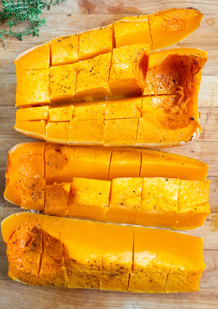 quartered roasted butternut squash on a cutting board