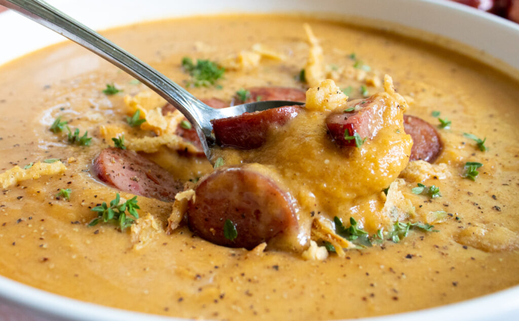 close up of sweet and savory roasted butternut squash soup with sausage and french fried onions in a white bowl on a spoon