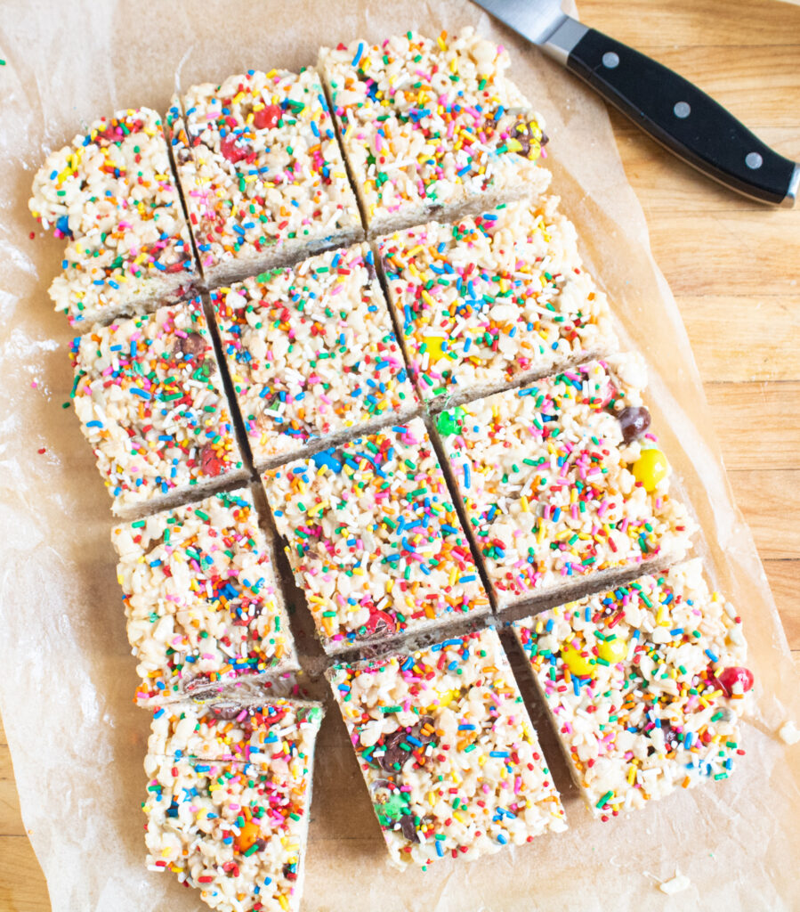 9x13 block of cut up rice krispie treats on parchment paper on a butcher block cutting board