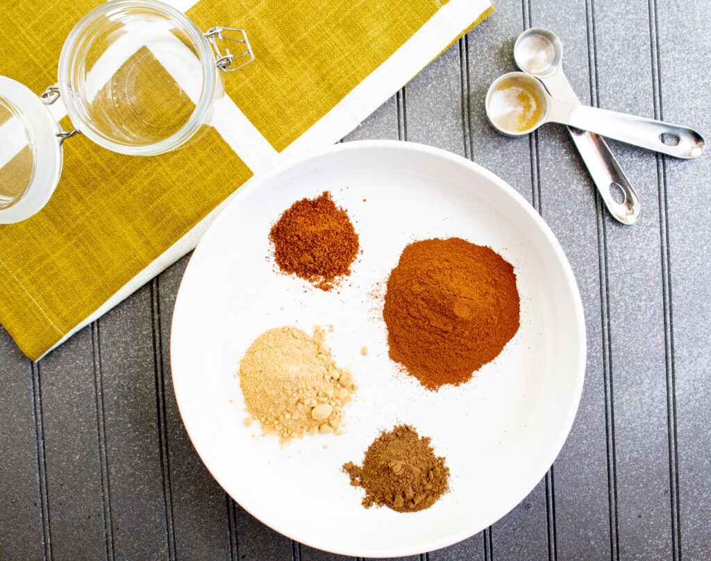 pumpkin pie spice ingredients on a white plate with measuring spoons and glass jar