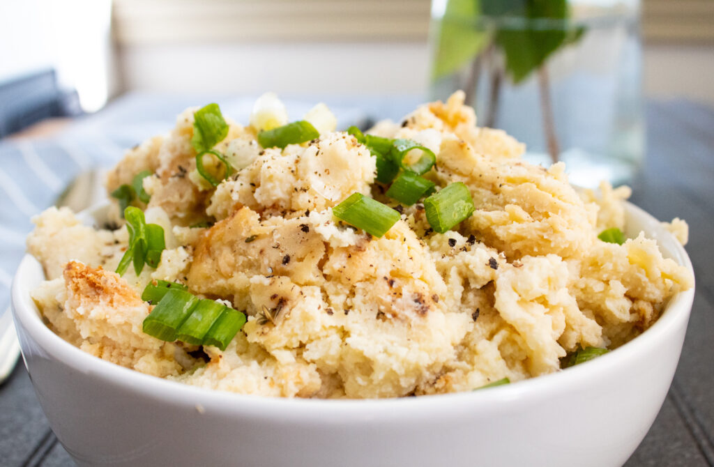 delicious comfort mashed potato cauliflower casserole in a white bowl with green onions