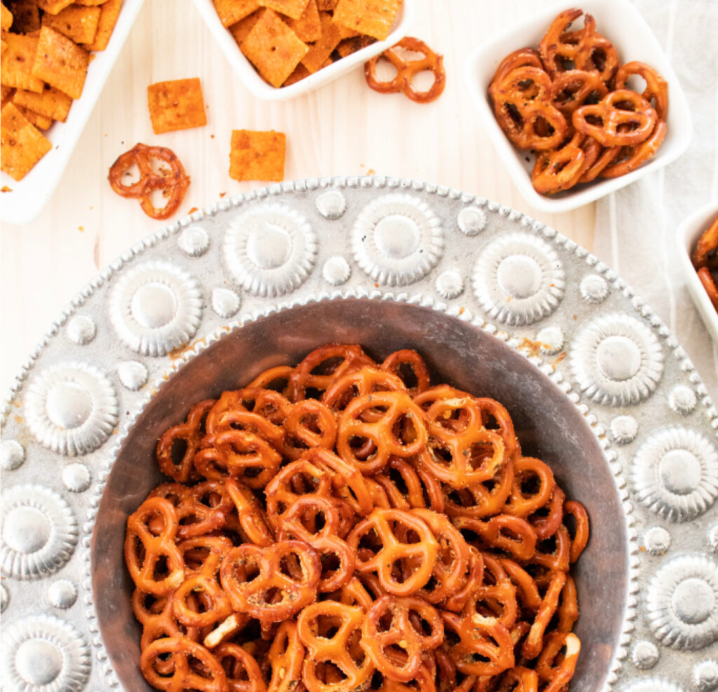 overhead zesty Italian seasoned mini pretzels in a silver serving bowl with feisty cheddar mini crackers