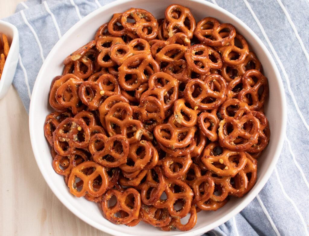overhead zesty Italian seasoned mini pretzels in a white bowl on a blue towel