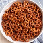 zesty Italian mini pretzels in a white bowl on a blue towel