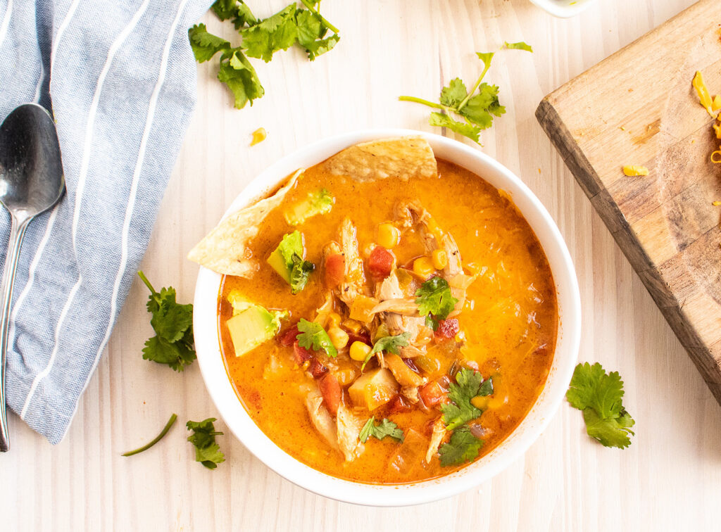 chicken tortilla soup in a white bowl with cilantro and chips