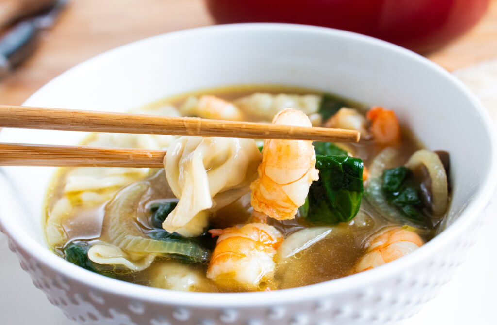 easy 30 minute shrimp wonton soup in a white bowl with chop sticks
