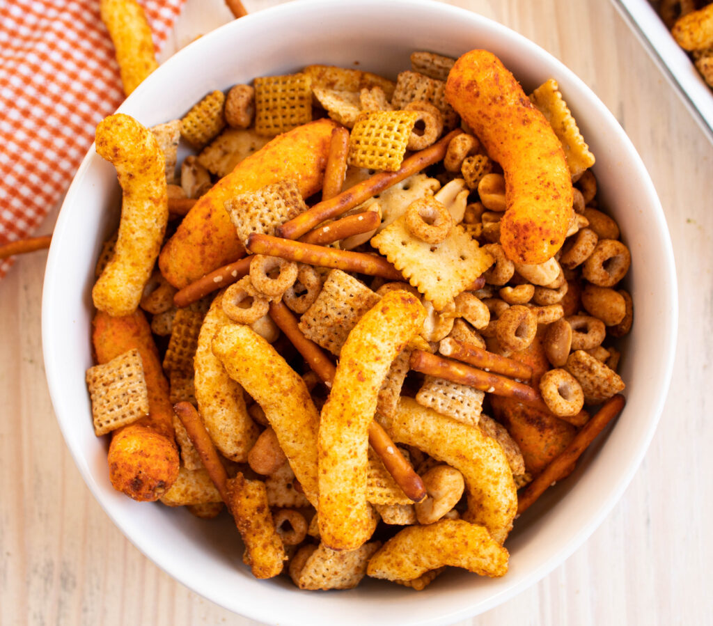 overhead homemade chex mix recipe with Cheetos in a white bowl
