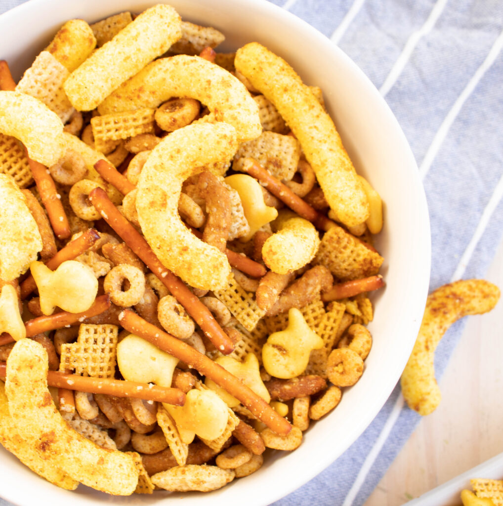 curry cheese puff chex mix with goldfish in a white bowl on a blue and white striped towel