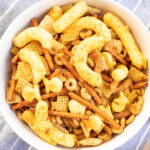 overhead picture of curry cheese puff chex mix in a white bowl