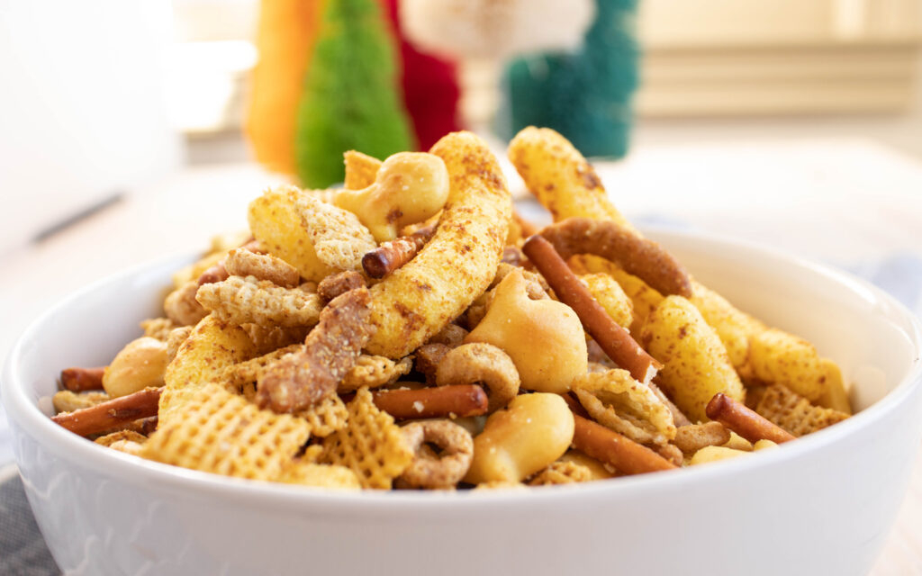 closeup side view of curry cheese puff chex mix in a white bowl