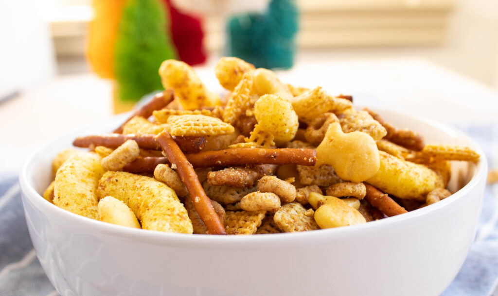 curry chex mix with seseme sticks and goldfish in a white bowl